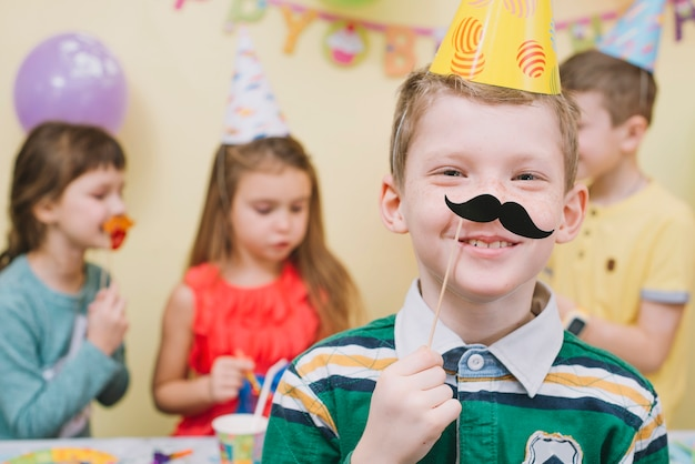 Boy wearing paper moustache on birthday party