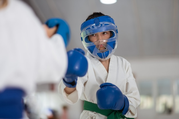 Boy wearing protective helmet and gloves boxing with friend