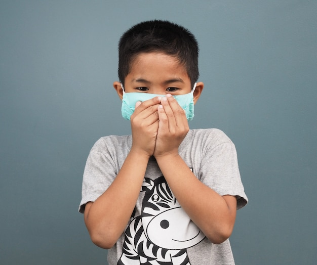 A boy wearing a protective mask while covering his mouth while coughing.