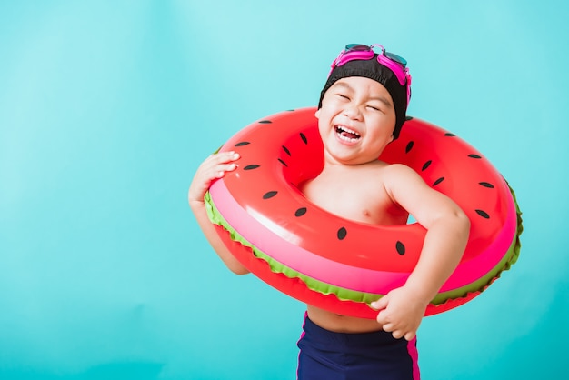 Boy wearing swimsuit holding beach watermelon inflatable ring