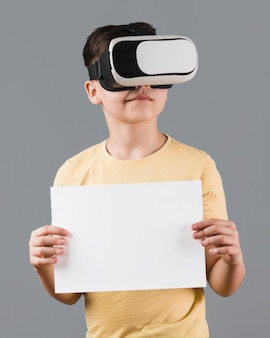 Boy wearing virtual reality headset and holding blank paper