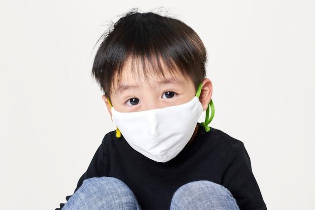 白いフェイスマスクを身に着けている少年