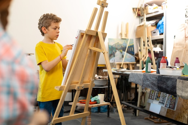Boy wearing yellow t-shirt painting on drawing easel