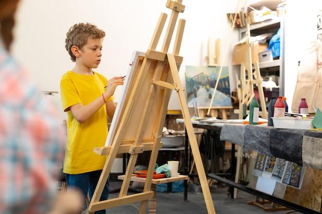 Мальчик в желтой футболке рисует на мольберте