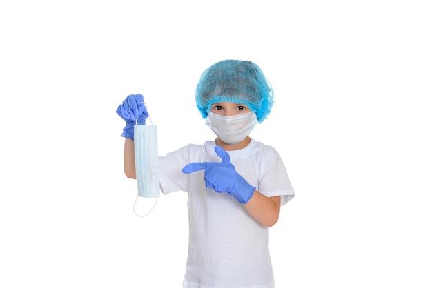 Мальчик носит защитную маску и латексные перчатки и жестикулирует надеть маску в борьбе с коронавирусом.
