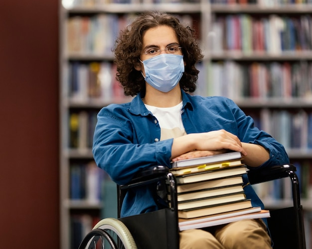 Boy in wheelchair holding a bunch of books