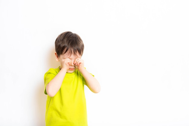 A boy on a white background rubs his eyes with his hands . the child wants to sleep . article about hands and eyes. dirty hand. a child's dream. eye disease . a boy on an isolated wall