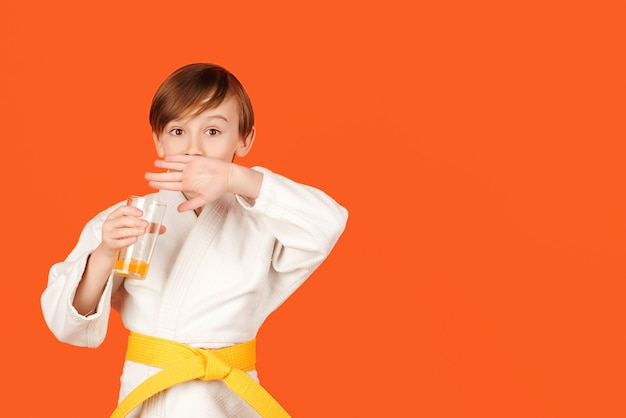 Boy in white kimono drinks water kid practicing karate on color background kid sport concept