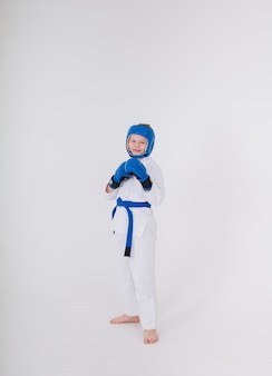 Boy in a white kimono, sports helmet, boxing gloves stands in a pose on a white background
