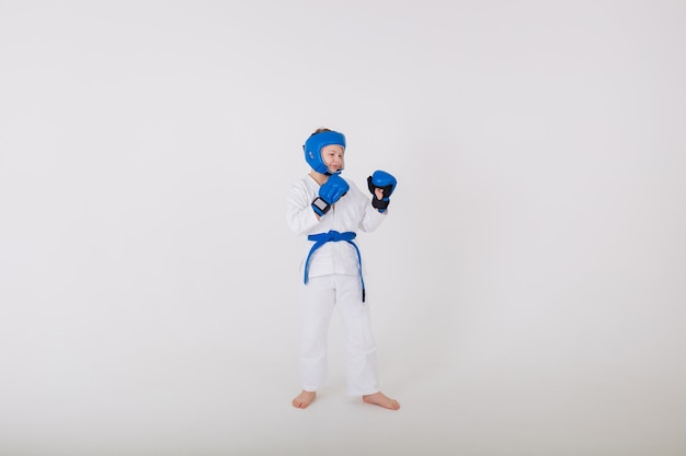 Boy in a white kimono and wearing gloves and a helmet stands sideways on a white wall
