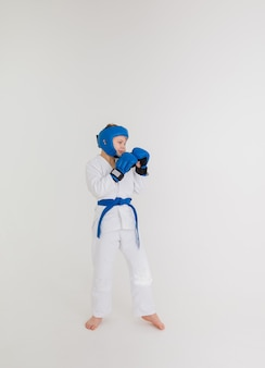 A boy in a white kimono with a blue belt stands sideways in a pose on a white background