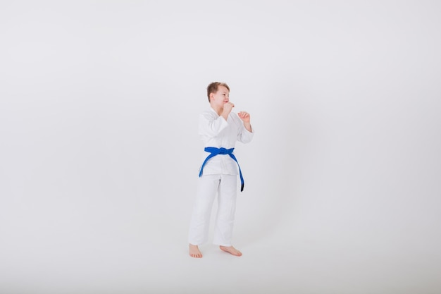 Boy in a white kimono with a blue belt stands sideways in a pose on a white wall