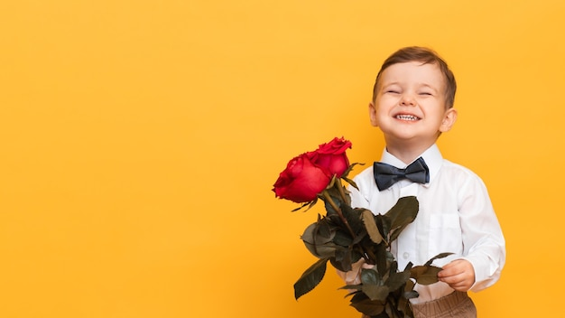 Boy in a white shirt, pants and a bow tie holds in his hands bouquet a red roses. a gift for my mother