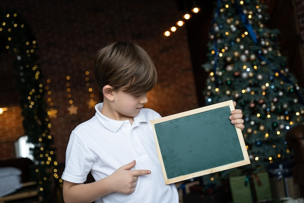 A boy in a white shirt stands by the christmas tree and holds a board with a blank space for text. christmas holidays concept