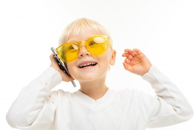 Boy on a white surface in yellow glasses chatting fun on the phone, laughing