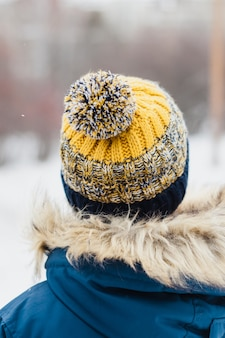 Boy in winter knitted hat, winter hat and winter walk, hiking