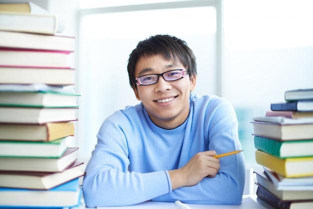 Мальчик с большой улыбкой в библиотеке