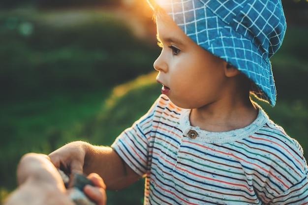 彼の両親の手から何かを取っている青い帽子を持つ少年