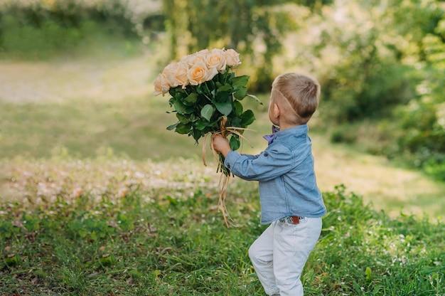 Мальчик с букетом белых роз в руках на фоне зелени.