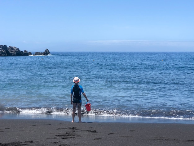 バケツを持つ少年は黒砂のビーチに立って海を見ています
