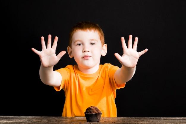 チョコレートカップケーキを持つ少年