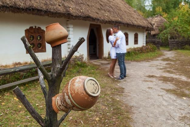 Мальчик с девушкой в национальной украинской одежде целуются возле старой избы