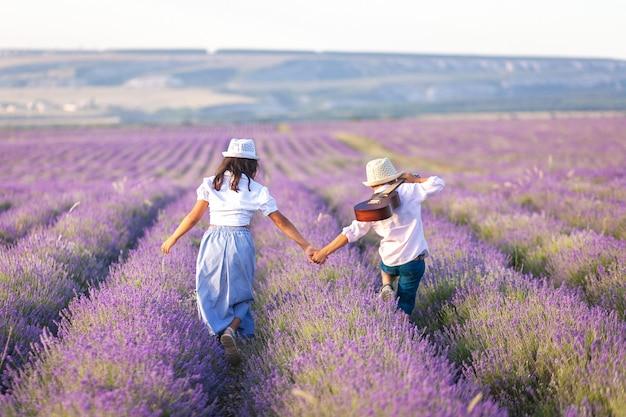 기타를 가진 소년과 소녀는 라벤더 밭에서 손을 잡고 산책