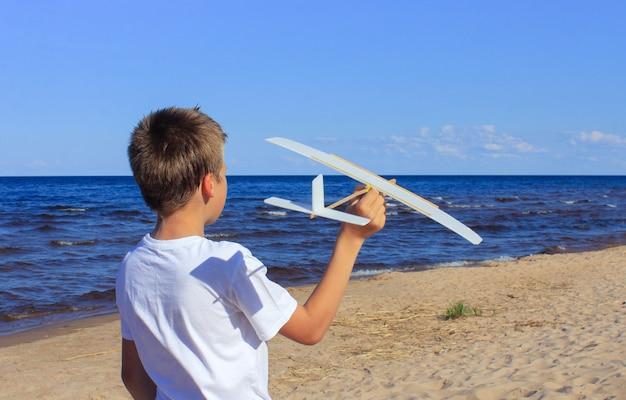 海岸に自家製の飛行機を持つ少年