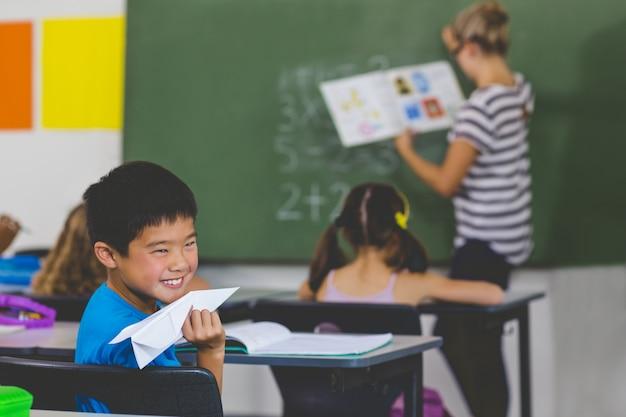 教師が教室で教えている間紙飛行機を持つ少年