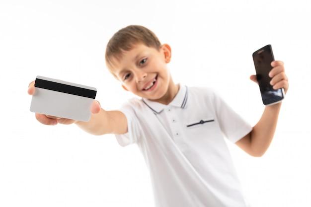 彼の手に電話を持つ少年は白のモックアップでクレジットカードを差し出します
