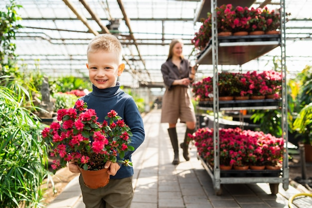 鉢植えの植物を持つ少年と花のカートを持つ彼のお母さん