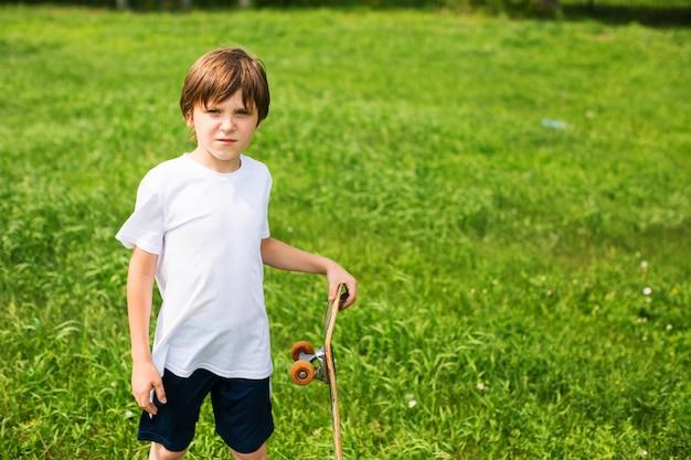 Мальчик со скейтбордом, на фоне травы