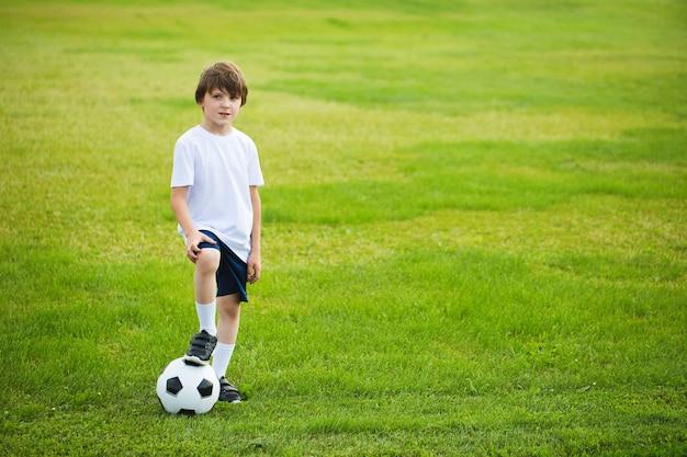 サッカー場でサッカーボールを持つ少年