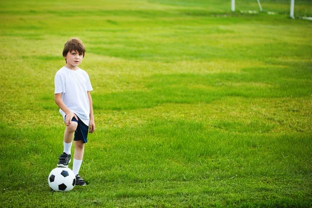 フィールド上にサッカーボールを持つ少年