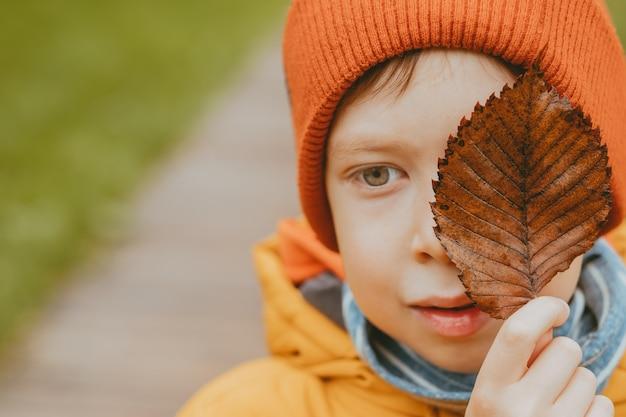 秋に顔に枯れた葉を持つ少年。秋のテーマ。男の子の手に乾燥した紅葉。悲しいトピック。赤い帽子と黄色いジャケットの少年。