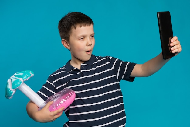 青い背景でselfieを取る飾られたおもちゃを持つ少年