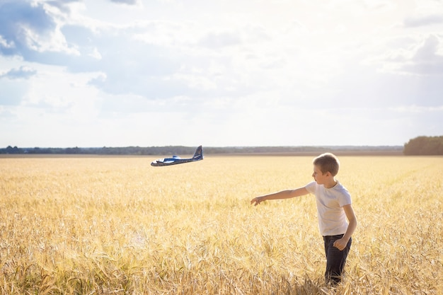 Boy with airplane on meadow