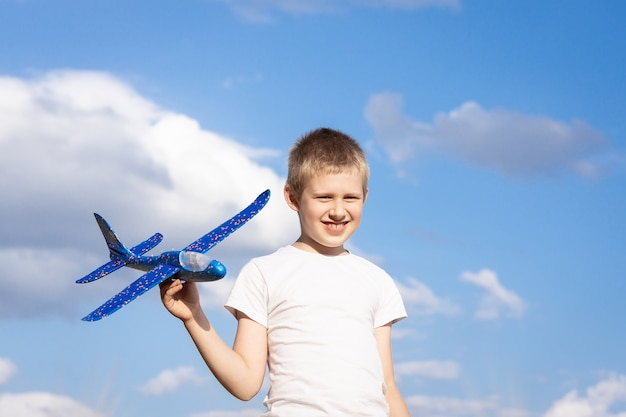 Boy with airplane on sky background