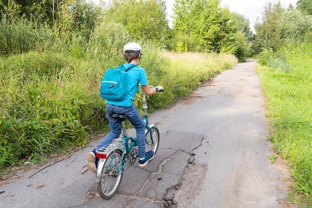 Мальчик с рюкзаком на велосипеде на проселочной дороге с зелеными деревьями сзади