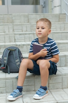 A boy with a backpack stands on the steps in front of the school