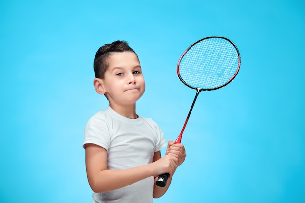 The boy with badminton rackets outdoors
