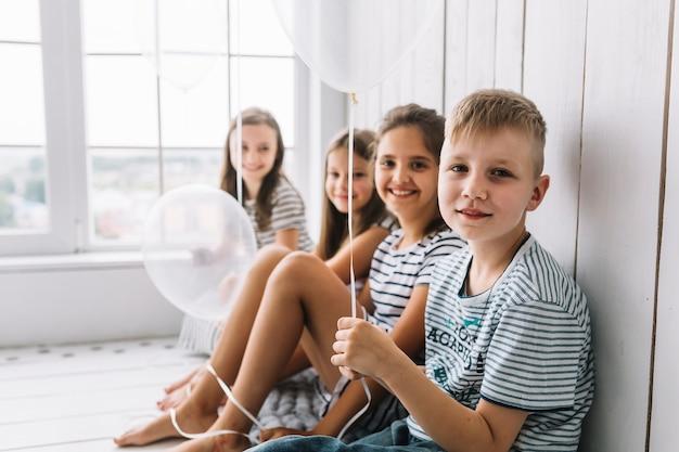 女の子の近くに座っている風船を持つ少年