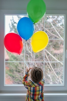 Boy with balloons in front of window
