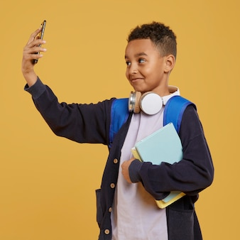 Boy with blue backpack taking a self photo