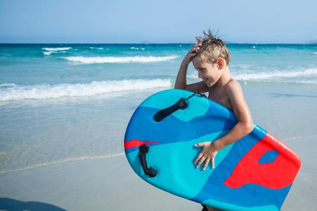 Мальчик с бодибордом на пляже
