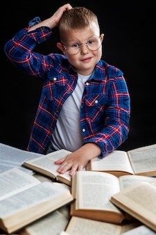 A boy with books sits at the table. smiling fat schoolboy with glasses. back to school. vertical.