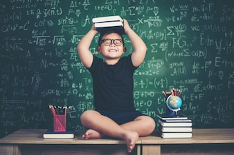 Boy with books sitting near green chalkboard