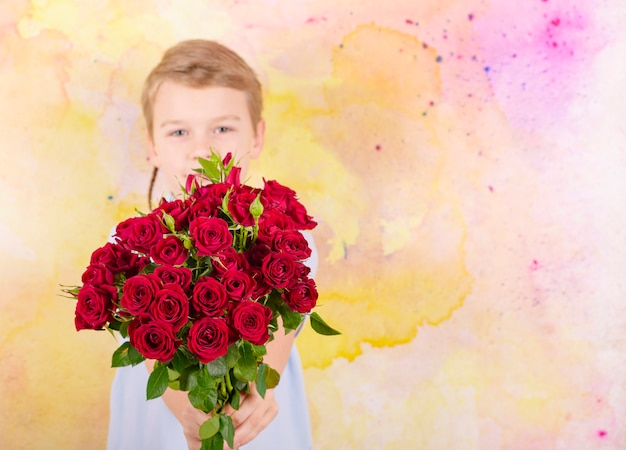 Boy with a bouquet of red roses as gift for mother's day or valentine's day