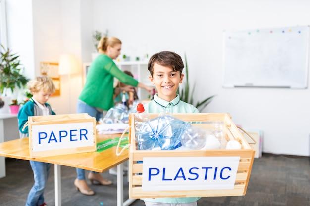 Мальчик с коробкой. темноволосый красивый школьник стоит с коробкой из пластика после сортировки в школе