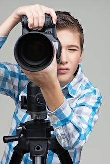 写真を撮るカメラを持つ少年。三脚にデジタル一眼レフカメラを持った少年。